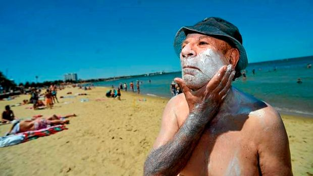 Rub it in: Chris Nesnas lathers on the sunscreen at St Kilda beach on Monday.