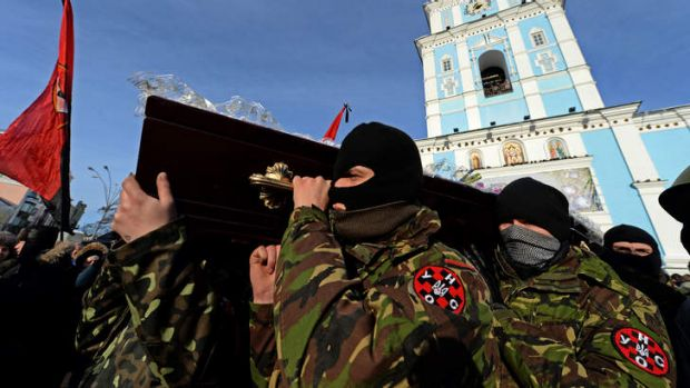 Violent end: Ukrainian protesters carry the coffin of Belarussian protester Mikhail Zhiznevsky, who was killed in recent ...