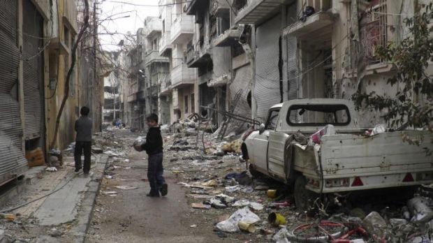 Children play along a street amid damaged buildings in the besieged area of Homs.