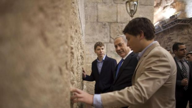 Girlfriend row: Israeli Prime Minister Benjamin Netanyahu, prays with his sons Yair, background, and Avner, right.