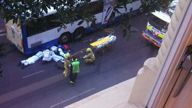 Trapped under a bus: paramedics treat the woman.