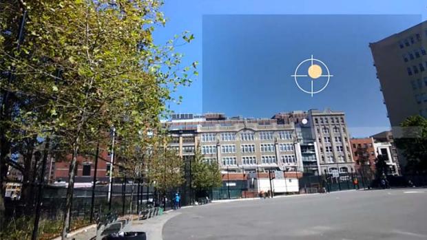 A Google Glass user takes aim at a virtual clay pigeon.