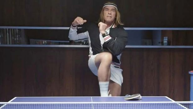 Arnold Schwarzenegger wears a long blond wig and poses as a ping pong player.