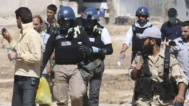 UN chemical weapons experts wearing gas masks carry samples collected from one of the sites of an alleged chemical ...
