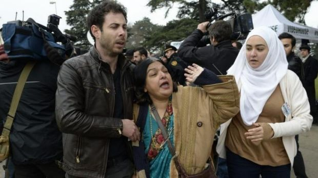 Ms Khan, escorted away by friends after trying to speak with members of the Syrian regime in Geneva.