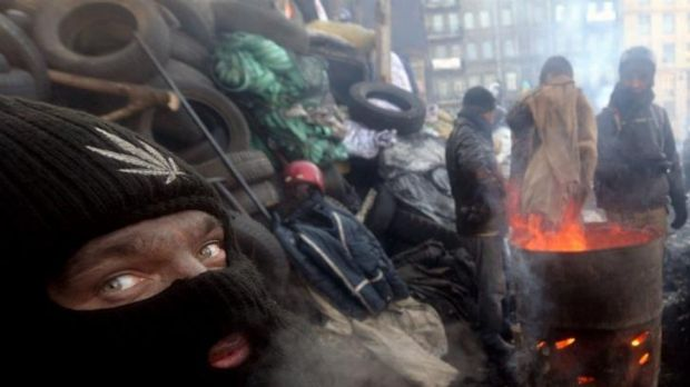 Anti-government protesters warm themself at a barricade in Kiev on January 30. A bill passed by Ukraine's parliament to ...
