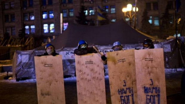 """Opposition supporters wearing protective gear hold wooden shields during """"training"""" at  Kiev's Independence Square."""