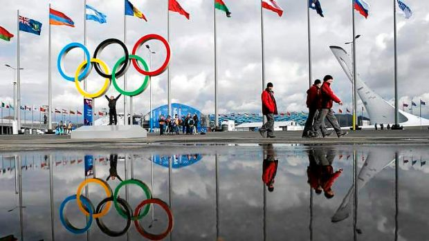 People walk past as the Sochi Olympic rings and the cauldron for the Olympic flame are reflected in a puddle of water on ...