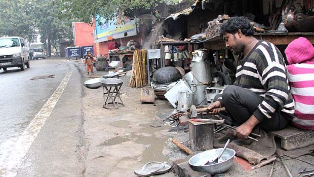 A better life: Vikram working outside his family's home, which is wedged between a stinking rubbish dump and a busy road.