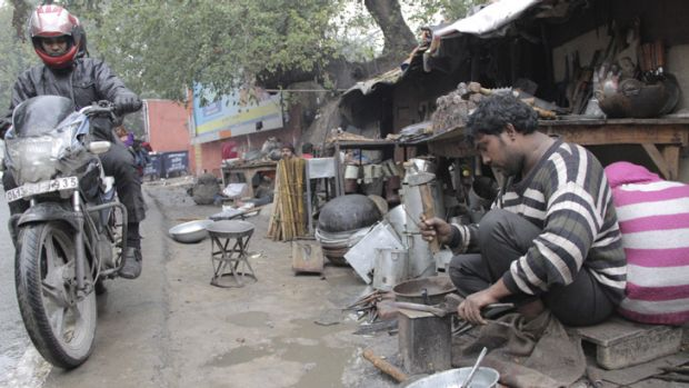 Vikram, a Rajasthani blacksmith and member of the nomadic Gadia Lohar tribe, works outside his home, which is built on ...
