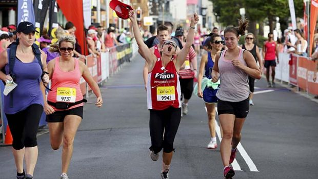 Runners cross the finish line in Manly.