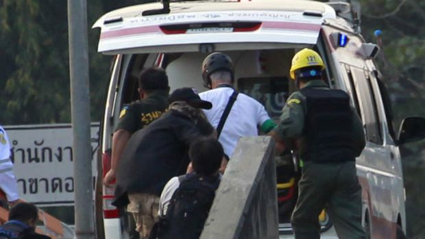 US journalist James Nachtwey, second right in white shirt, is taken to an ambulance after he received a minor injury ...