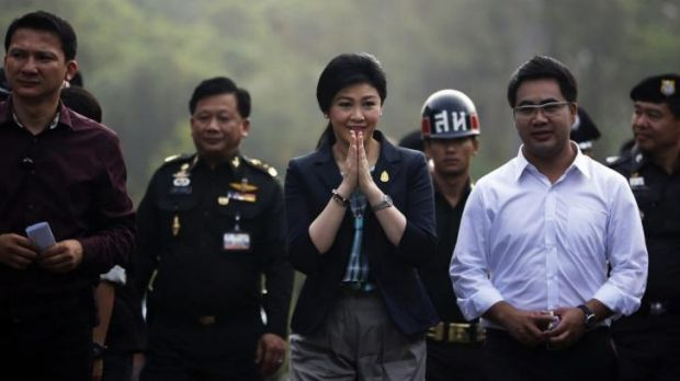 Prime Minister Yingluck Shinawatra, centre, greets people as she arrives to a polling station to cast her vote.