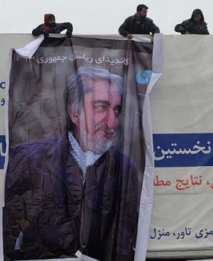 Undaunted: Afghan workers install a campaign banner of Abdullah Abdullah in Kabul.