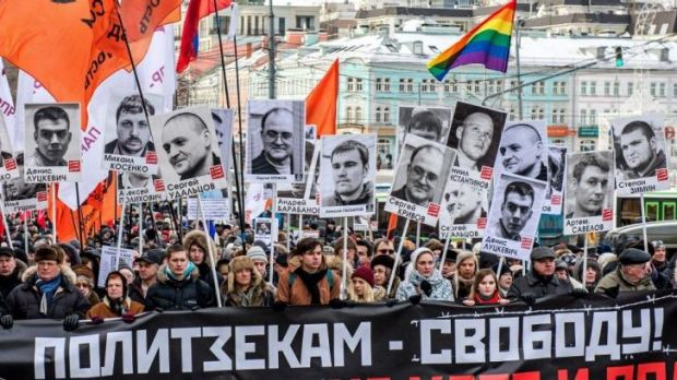 People carry pictures of political prisoners and a banner reading 'Freedom for political prisoners!' during an ...