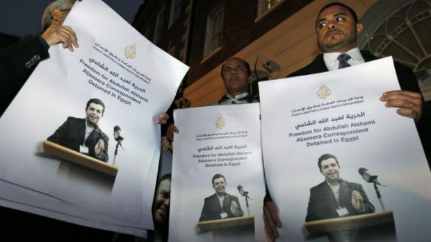 Demonstrators hold placards with pictures of Al-Jazeera Arabic network journalist Abdullah Al Shami who was detained ...