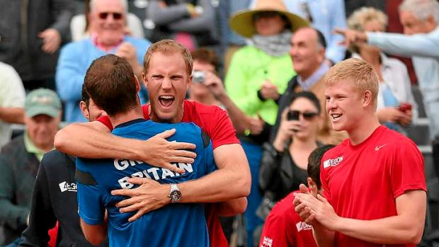 Brit force: Andy Murray of Great Britain is hugged by team mate Dominic Inglot after his four set victory against Sam ...
