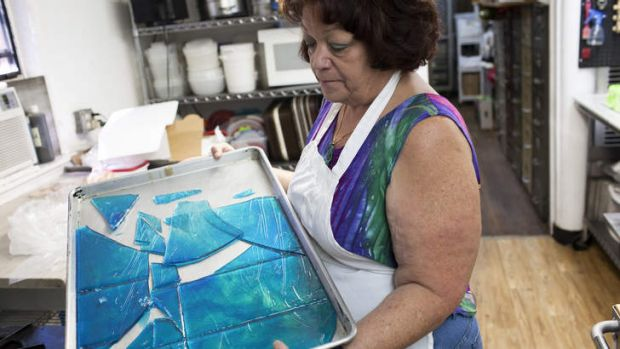 Debbie Ball, owner of The Candy Lady, holds rock candy made to resemble the blue meth from the TV show <i>Breaking ...