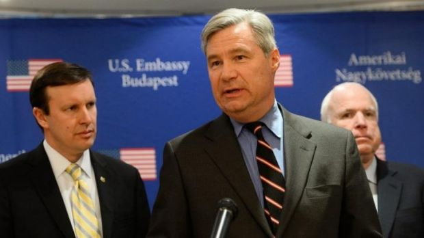 Conflicting views: US Senator Sheldon Whitehouse (C) addresses journalists as senators John McCain and  Chris Murphy look on.