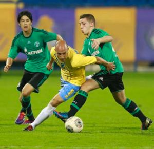Mark Bresciano, playing for Qatar's Al-Gharafa club, fights for the ball with Schalke 04's Atsuto Uchida (left) and ...