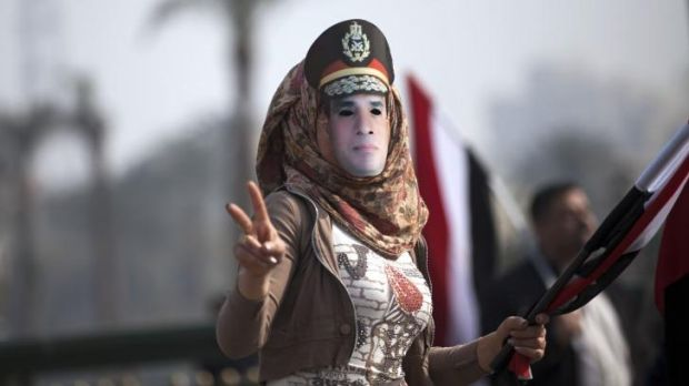 A woman wears a mask depicting Defence Minister Field Marshal Abdel Fattah Al-Sisi.