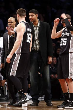 Australian Boomers centre Aron Baynes talks to San Antonio Spurs injured forward Tim Duncan during a timeout against the ...