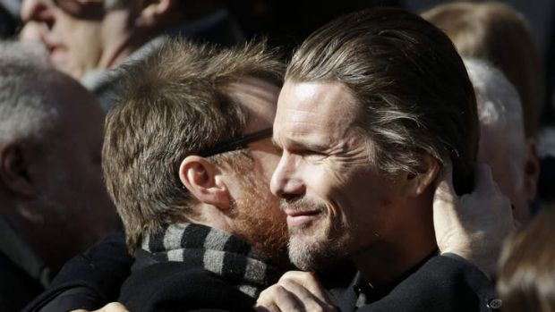 Ethan Hawke, right, exchanges a hug with an unidentified man following the funeral of actor Philip Seymour Hoffman at ...