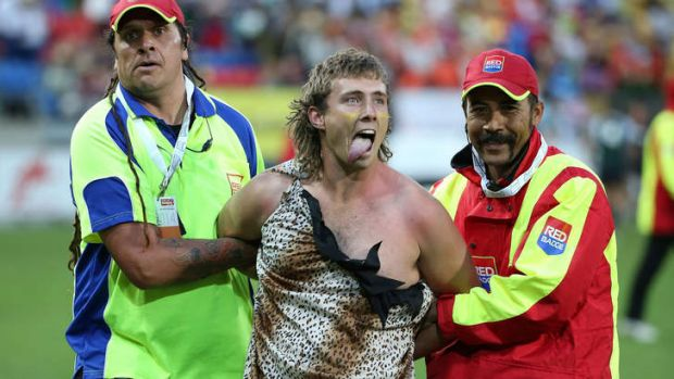 A spectator dressed as Tarzan is ejected from the stadium after getting onto the outer field during the parade of ...