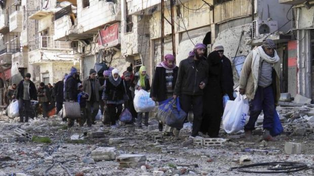 'Heart of the revolution': Civilians carry their belongings as they walk towards a meeting point to be evacuated from Homs.