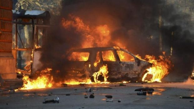 Simmering anger: A car burns as anti-government protesters clash with police in Sarajevo.