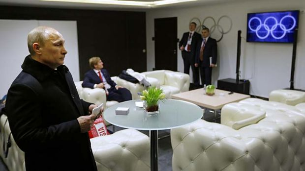 Snow-fake ....  Russian president Vladimir Putin watches footage of the ceremony showing five 'complete' Olympic rings.