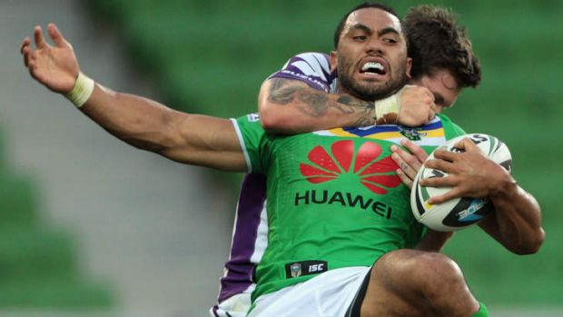 Caught: Canberra's Bill Tupou is held by Ben Hampton.