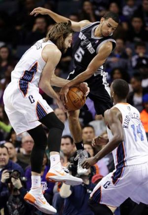 Cory Joseph of the San Antonio Spurs (centre) battles with Josh McRoberts of the Charlotte Bobcats (left) for a rebound ...