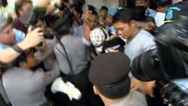 Schapelle Corby, wearing a checked hat, leaves Kerobokan prison.