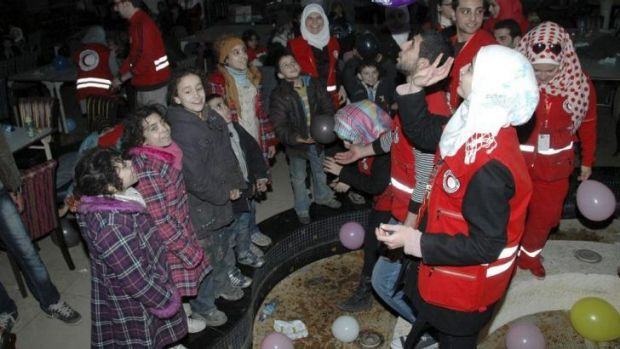 Respite: Members of the Syrian Red Crescent play with children who have fled Homs.