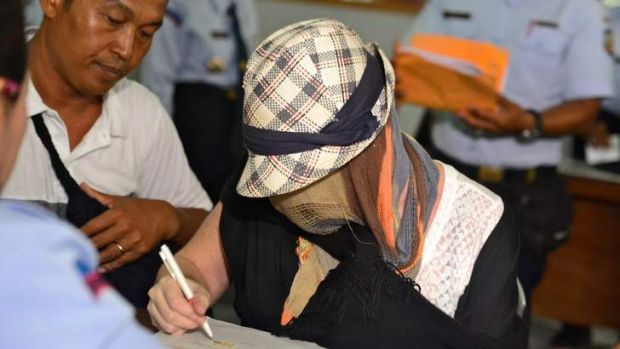 Schapelle Corby signs paperwork at the Corrections Bureau.