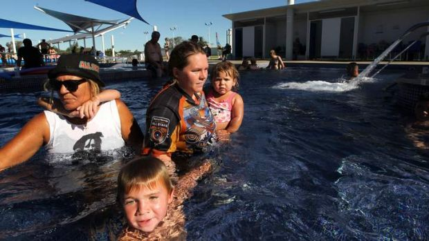 Cooling off: Shane Weatherall, 5, with his nan Marlene Wood (left) and his mother Lee Stothard holding his sister
