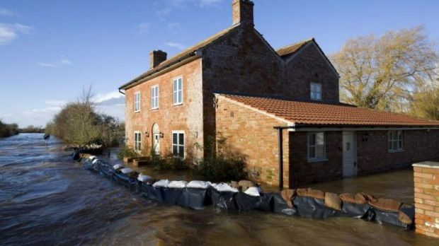Flood waters engulf a house with a wall of sandbags around it in Burrowbridge.