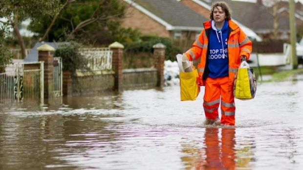 A man walks through flooded streets in the village of Moorland in Somerset, England.