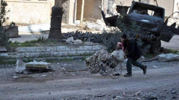 A civilian in a wheelchair is helped by an armed man ahead of being evacuated from the city of Homs.