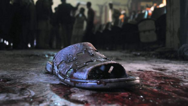 Ruthless ... A blood-stained shoe of a victim lies on the ground at the site of a grenade attack on a crowded cinema ...