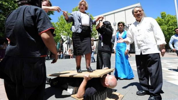Minister Joy Burch helping promote an earlier Multicultural festival - by standing on Kung Fu grandmaster Neal Hardy ...