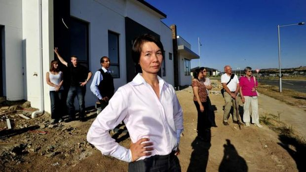 Tanya Nguyen, of Wright, and other affected home buyers from across Canberra gather outside her unfinished house; from ...