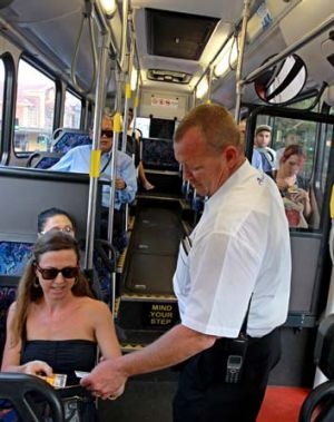 Just the ticket: Transport officer Arron Cutugno checks on bus passengers at Bondi Junction.