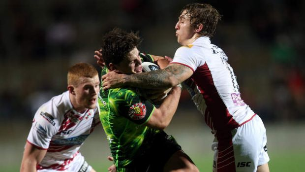 Got him: Warriors player Jarrod Wilson is tackled by Sam Powell of Wigan at Waikato Stadium on Wednesday night.