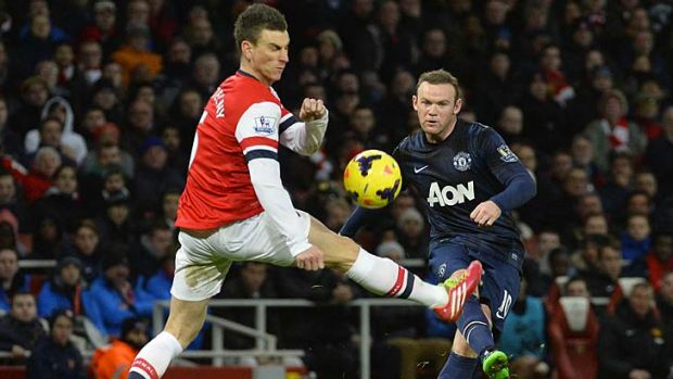 Manchester United's Wayne Rooney (R) is challenged by Arsenal's Laurent Koscielny.
