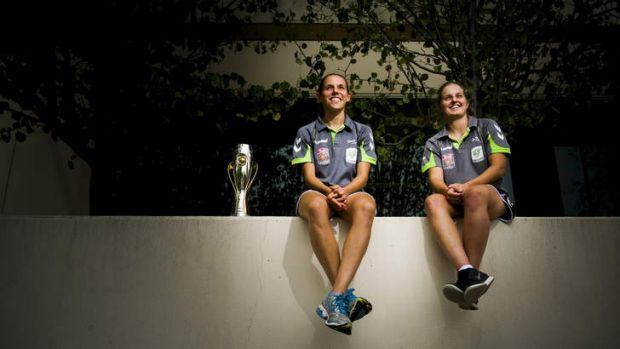 Canberra United players Nicole Sykes and Ellie Brush with the 2012 W-League trophy ahead of their semi-final against ...
