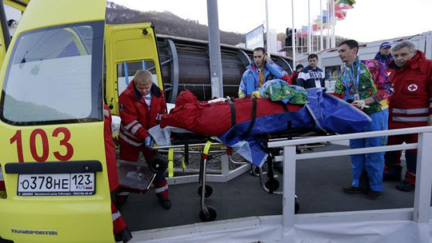 Broken legs: A track worker is loaded into an ambulance after he was injured when a forerunner bobsled hit him before ...
