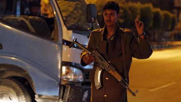 A policeman guards the entrance to the central prison in Sanaa, Yemen, where al-Qaeda inmates were freed in a deadly ...