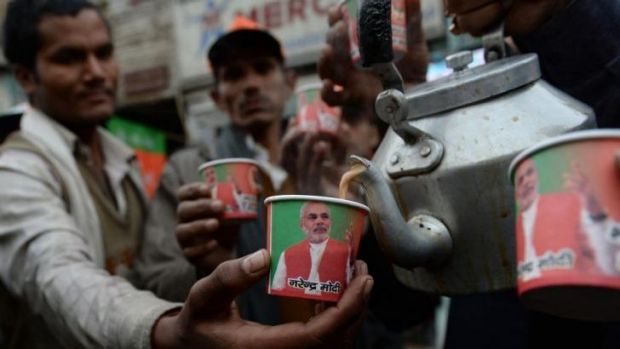 Paper cups bearing the portrait of prime ministerial candidate Narendra Modi are pictured as party workers distribute ...
